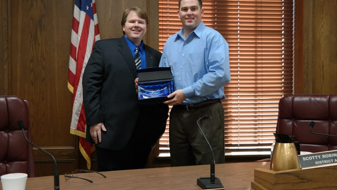 OPPJ President Scotty Robinson (at right) receives a Community Leadership Award from Woodmen representative Jon Elliott.