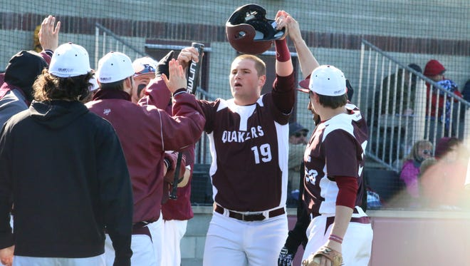 Eric Elkus of the Earlham College baseball team is congratulated by his teammates.