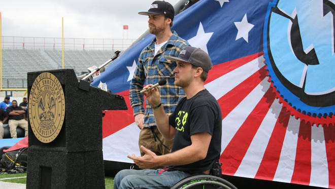 Nitro Circus freestyle motorcyclist Bruce Cook speaks to a crowd of reporters while Steve Mini looks on at Independence Stadium Thursday afternoon.