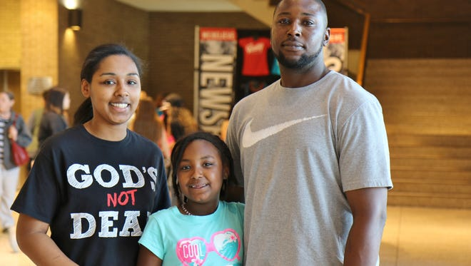Shamira McIntyre, Chad Frame and Kimora Frame pose for a photo while waiting for the Newsboys concert Sunday at the Carl Perkins Civic Center.