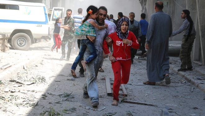 A Syrian family runs for cover amid the rubble of destroyed buildings following a reported airstrike on the Syrian city of Aleppo, on April 29, 2016.