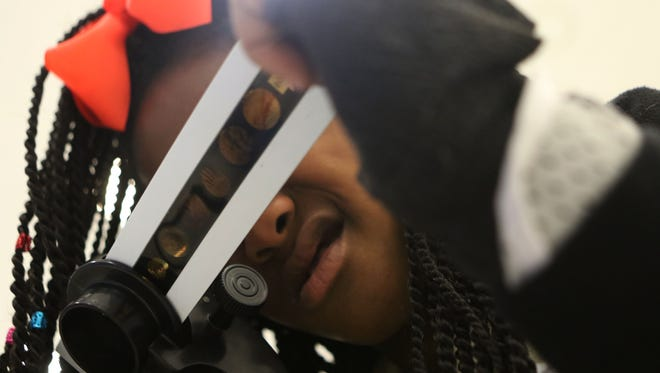 Micaela Elmore, 10, looks through a microscope at slides that depict fossilized organisms during her class' time with the Mobile Oilfield Learning Unit (MOLU) at J.S. Clark in Monroe on Tuesday. MOLU is a traveling, interactive exhibit that teaches kids about the science and technology of working in oilfields.