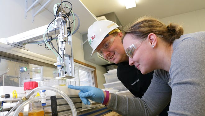 LG&E and KU employee Dr. David Link works with a researcher from the University of Kentucky to examine equipment used in the carbon capture process.