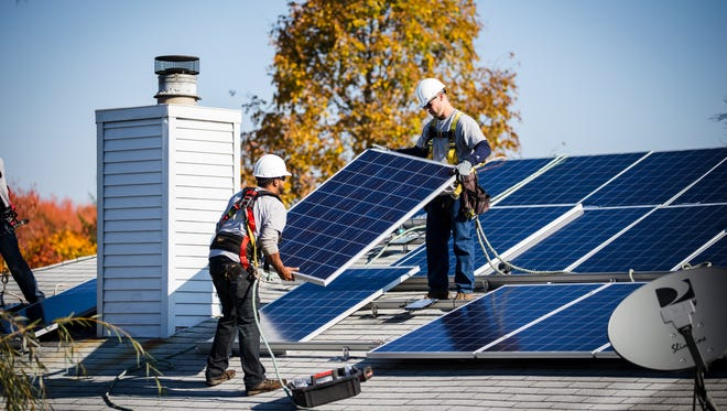 An NRG Home Solar crew installs solar panels at a home in Marlboro in 2014.