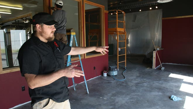 Co-owner and treasurer Jim Smiley explains where tables will be placed in the addition to the taproom.