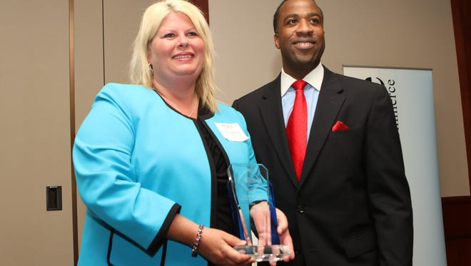 Christine Bartlett, leader of the IBM Services Center in Monroe, left, accepts the Thomas H. Scott Award of Excellence from Chairman of the Monroe Chamber of Commerce William Smart, right, at the University of Louisiana at Monroe Conference Center on Thursday, May 19, 2016.