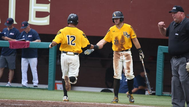 Southern Miss' Jake Sandlin, left, and Hunter Slater celebrate after scoring a run against South Alabama Sunday, but the Golden Eagles fell to the Jaguars, 7-5.