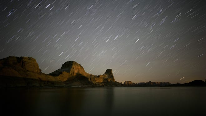 Stars appear to streak through the night sky above Gunsight Butte in Glen Canyon National Recreation Area in a long exposure image taken at Lake Powell.