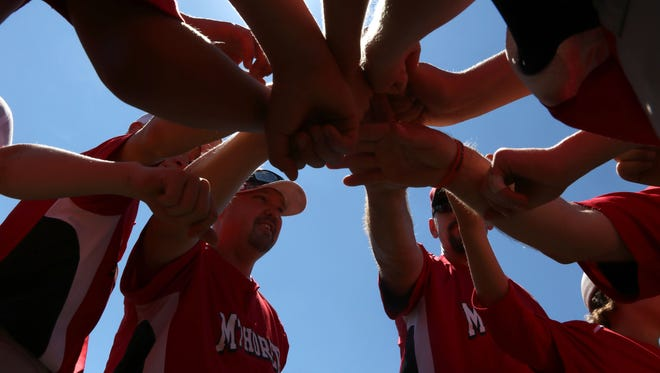 Teammates put their hands in after a successful game during the opening day of Small Town Baseball State Championships in Marshfield, June 24, 2016.