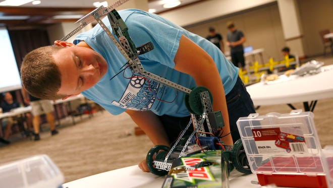 Thomas Beer, 15, looks over the gear motor for his robot during the VEX robotics camp at the Kehoe Center in Shelby on Tuesday.