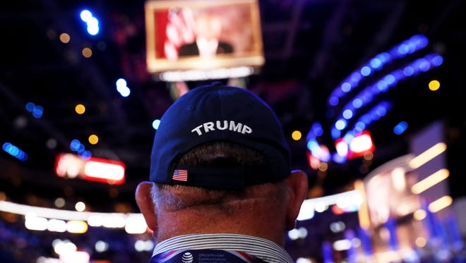 A delegate watches Republican presidential candidate Donald Trump speak on a screen from New York City, on the second day of the Republican National Convention on July 19, 2016 at the Quicken Loans Arena in Cleveland, Ohio.
