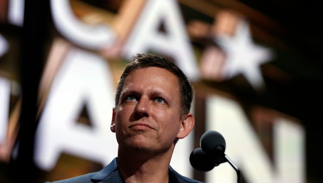 Billionaire tech investor Peter Thiel looks over the podium before the start of the second day session of the Republican National Convention in Cleveland, Tuesday, July 19, 2016.
