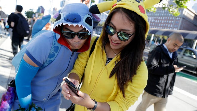 People costumed as the game's characters participate in a Pokemon Go search during a gathering of players July 20, 2016, in San Francisco.