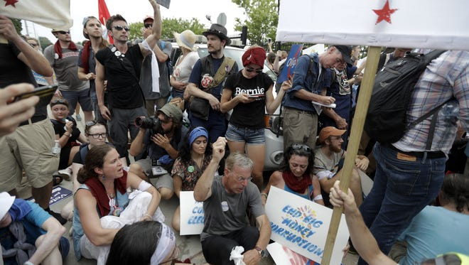 Demonstrators sits down near the AT&T Station as police look on, Monday, July 25, 2016, in Philadelphia, during the first day of the Democratic National Convention. (AP Photo/Matt Slocum)
