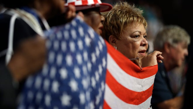 Florida delegates hold up a flag during the national anthem during the third day session of the Democratic National Convention in Philadelphia, Wednesday, July 27, 2016. (AP Photo/John Locher)