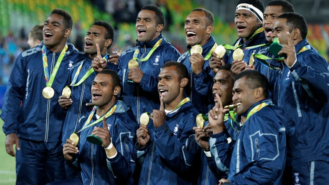 Fiji rugby players show off their gold medal after defeating Britain in mens rugby sevens at the 2016 Summer Olympics in Rio de Janeiro, Brazil, Thursday, Aug. 11, 2016.