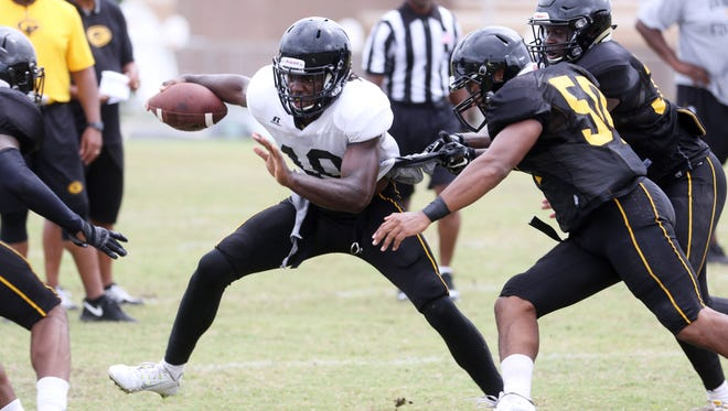 Chad Williams attempts to maintain possession of the ball as other players tackle him during a scrimmage at Grambling's football practice on Saturday, August 13, 2016.