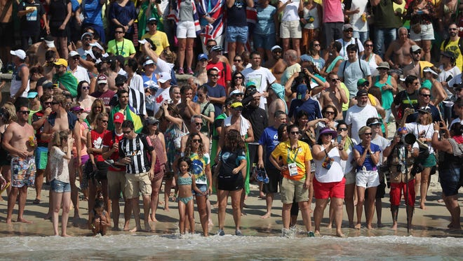 Fans look on from the beach during the women's 10K in the Rio 2016 Summer Olympic Games at Fort Copacabana on Aug. 15.