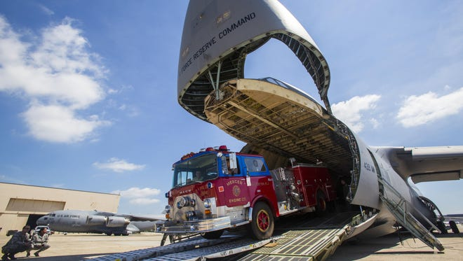 An Air Force reserve crew loads a donated fire truck into a cargo plan at Joint Base McGuire-Dix-Lakehurst for delivery to a volunteer fire department in need in Nicaragua.                                    .