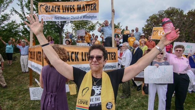 The Rev. Roberta Finkelstein holds up her hands in prayer during a rededication ceremony for First Unitarian Church's Black Lives Matter banners in Talleyville on Sunday, Aug. 21, 2016.