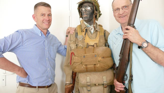 Jim Farrell (right) holds his late Uncle Matty's D-Day rifle. French Army Colonel Patrick Collet (left) discovered it.