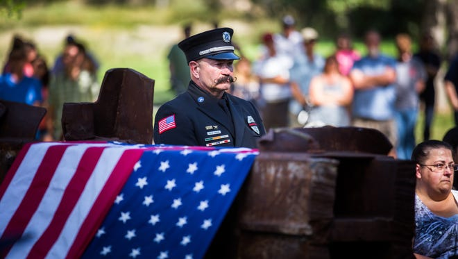 Bryan Hanson of the Poudre Fire Authority stands next to a beam that was a part of the World Trade Center buildings that fell on September 11, 2001.The beam will become part of a permanent memorial for the responders and victims.