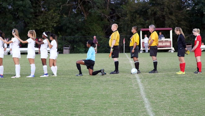 Brebeuf Jesuit goalkeeper Lauren Turner kneels during the national anthem before a game against Center Grove.