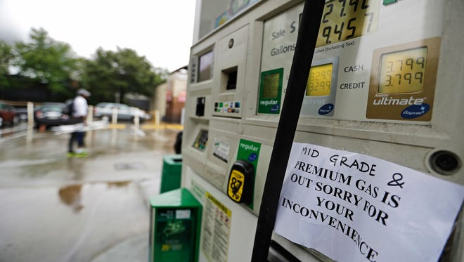 A gas station displays a sign informing customers it is out of certain grades of gasoline in Atlanta on Sunday. Oil prices are half of what they were about two years ago, but there is a downside.