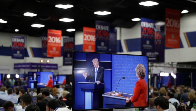 Democratic presidential candidate Hillary Clinton and Republican presidential candidate Donald Trump are seen on screens in the media center during the presidential debate, Monday, Sept. 26, 2016, in Hempstead, N.Y.