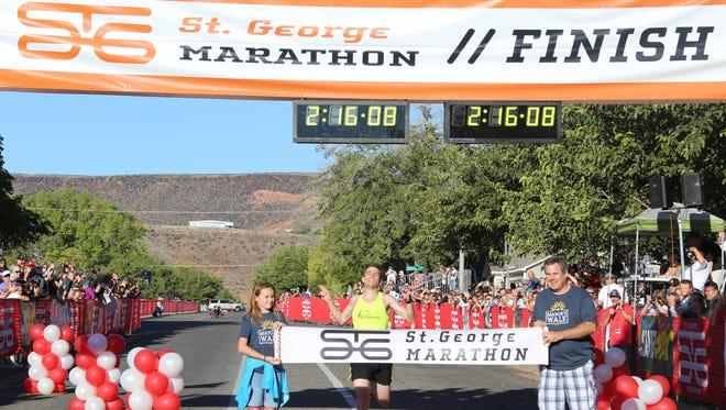 Riley Cook breaks the tape at the finish line as the top overall winner in the 40th annual St. George Marathon Saturday, Oct. 1, 2016.