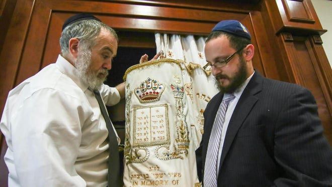 Rabbi Chuni Vogel (left) and Rabbi Motti Flikshtein prepare to return a covered Torah to the Aron Kodesh during preparations for Rosh Hashanah at the Chabad Center for Jewish Life, near Wilmington, on Sunday, Oct. 2, 2016.