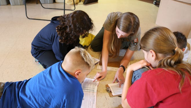 A park ranger assists 5th grade Virgin Valley Elementary students during a critical thinking exercise.