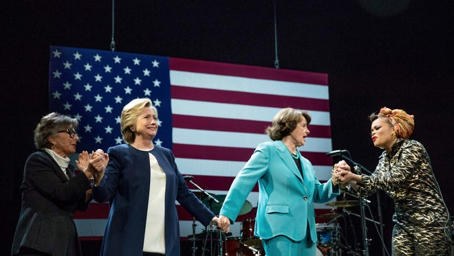 Democratic presidential candidate Hillary Clinton, second from left, accompanied by Sen. Barbara Boxer, D-Calif., left, and Sen. Dianne Feinstein, D-Calif., second from right, takes the stage after being introduced by singer Andra Day, right, at a fundraiser at the Civic Center Auditorium in San Francisco, Thursday, Oct. 13, 2016.