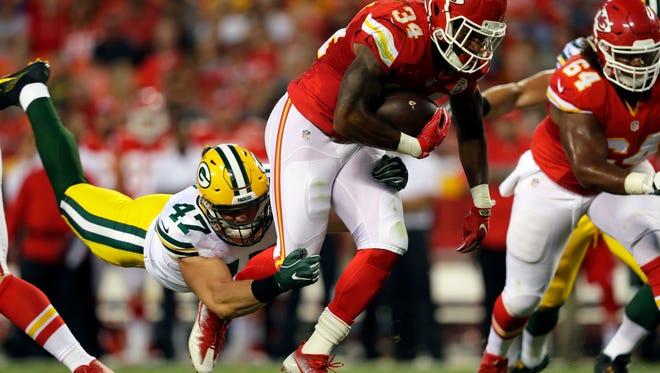 Running back Knile Davis looks to get past Packers linebacker Jake Ryan during a preseason game at Kansas City.
