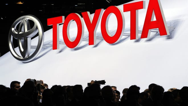 The logo of Japanese car manufacturer Toyota is displayed behind members of the media Toyota at the Paris Auto Show in Paris, France.