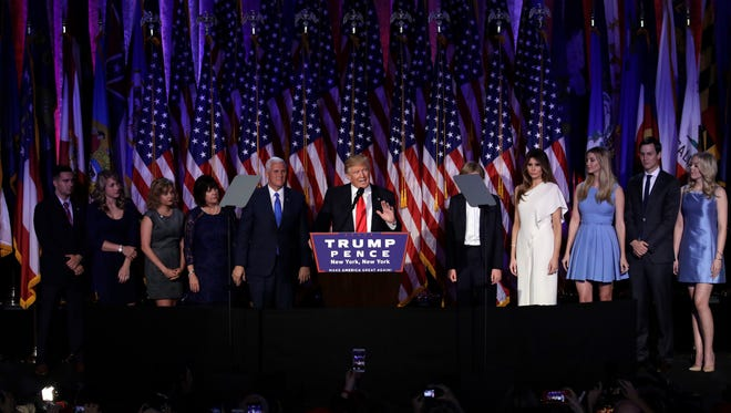 President-elect Donald Trump gives his acceptance speech during his election night rally as he is surrounded by his family and Vice-President-elect Mike Pence and his family, Wednesday, Nov. 9, 2016, in New York. (AP Photo/John Locher)