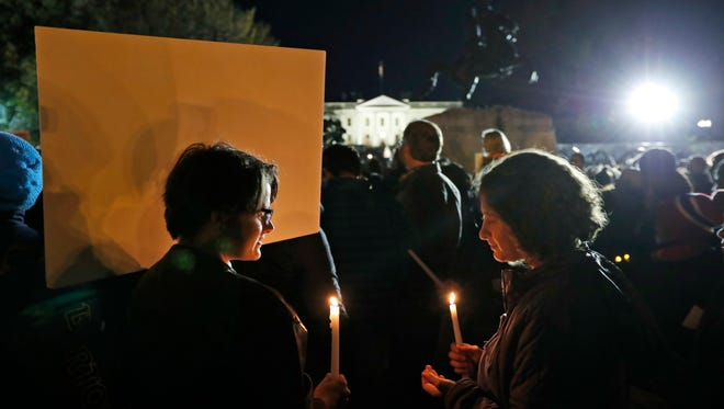 Elizabeth O'Brien, left, from Washington, and Hannah Allan, from New York, hold candles during an election protest in Lafayette Square Park in front of the White House, Saturday, Nov. 12, 2016 in Washington. (AP Photo/Alex Brandon)