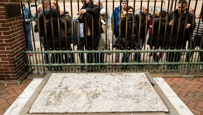 Tourists peer throughout a fence at the Benjamin Franklin's grave at the Christ Church Burial Ground in Philadelphia, Tuesday, Nov. 15, 2016. A fundraising campaign has been launched to save Franklin's damaged gravestone.