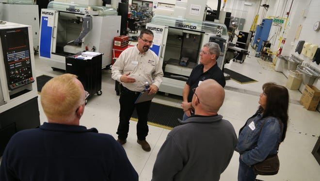 Fox Valley Technical College machine tool instructor Jeff Theys discusses the college's apprenticeship program to guests during National Apprenticeship Week.