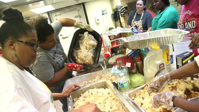 Dozens of volunteers help prepare a Thanksgiving Meal at Friendly House in this News Journal file photo.