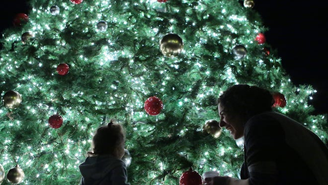 Lucy Coombs, left, and her mother Angela Naimou of Pendleton look at ornaments and lights moments after the Christmas Tree Lighting on Friday in Pendleton.