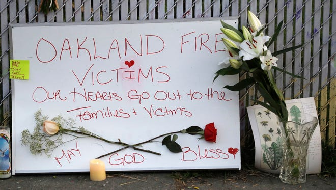 Signs and flowers adorn a fence near the site of a warehouse fire Monday, Dec. 5, 2016, in Oakland, Calif.