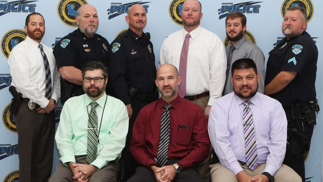 Officers with the Monroe Police Department sport the beards they grew for No Shave November during a portrait shoot at the Public Safety Center on Wednesday, December 7, 2016. Officers grew beards to raise awareness for early detection of cancer through screenings, particularly of the prostate and colon.  Back row, left to right: Detective Chris Bates, Major Doug Tarver, Lieutenant Trische Passman, Detective Jeremy Sturdivant, Detective Stephen Snowberger, Corporal Tony Walker. Front row, left to right: Crime Analyst Scott Rogers, Detective Matt Schmitz, Detective Darren Canales