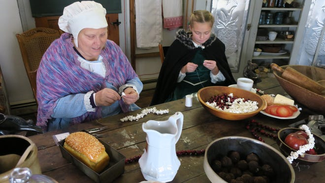 Cathy Haynes (left) and Karley Beeler string popcorn and cranberries to make decorative holiday garlands.