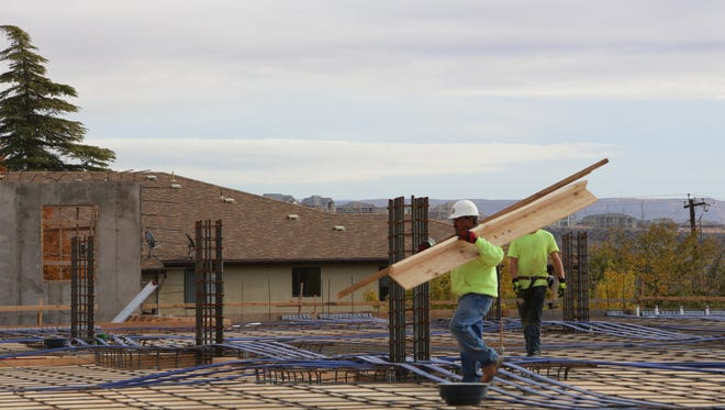 Crews with Bonneville Builders work on a new housing complex along Tabernacle Street near Dixie State University on Friday, Dec. 9, 2016.