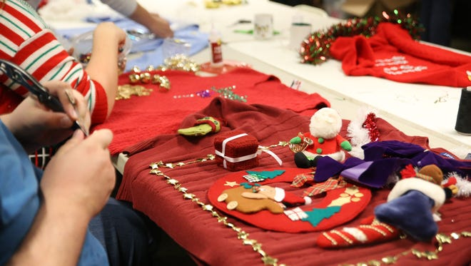 """Various Christmas decorations lay on South Knoxville's Jason King's """"ugly sweater"""" as he plans it out at Ijams Nature Center during the Goodwill sponsored Ugly Christmas Sweater Workshop on Dec. 13, 2016."""