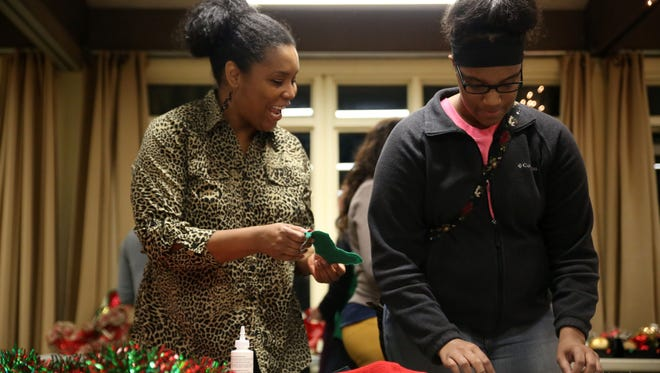 """At left Lyndsay Zachery shows Tashae Thomas a silly Christmas Ornament  she might use on her """"ugly sweater"""" at Ijams Nature Center during the Goodwill sponsored Ugly Christmas Sweater Workshop Tuesday, Dec. 13, 2016. Zachery is Thomas' """"Big"""" in the Big Brothers Big Sisters program."""