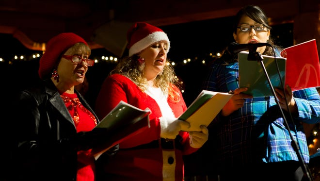 New Mexico State Gospel Choir members, from left, Michelle Casillas, Tresela Lee and Ashley Guerrero sing holiday carols at the Mesilla Christmas Eve and Luminarias event held December 24, 2016.