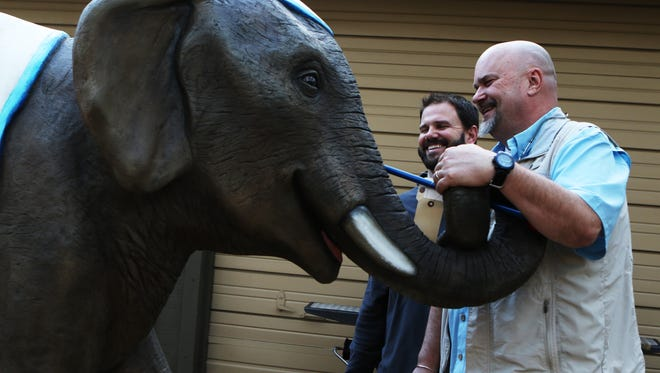 Doug Seegers and Matt West laugh as they study their reflections in the eyes of Betty, an elephant for Smiles Park at Kiroli was delivered on Tuesday, January 3, 2016. The park has been designed to be inclusive of kids and adults of all abilities. People with disabilities will be able to play alongside people without disabilities.