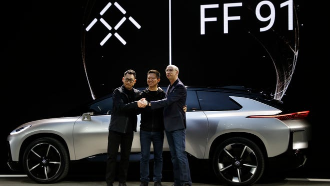 LeEco CEO YT Jia, center, poses with Nick Sampson, Faraday Future's senior vice president of product research & development, right, and Richard Kim, vice president of design, after unveiling the FF91 electric car at CES Tuesday, Jan. 3, 2017, in Las Vegas.
